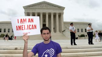 WASHINGTON D.C., June 23, 2016-- A man holds a placard during an immigration rally outside the Supreme Court in Washington D.C., the United States, on June 23, 2016. U.S. Supreme Court on Thursday delivered a heavy blow to the White House's immigration program by remaining in place a lower court's ruling that blocked the program. (Xinhua/Yin Bogu via Getty Images)