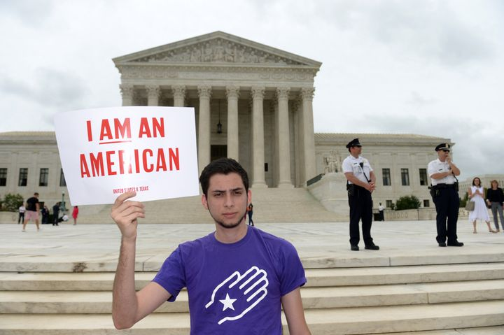 Immigration activist Julian Gomez of Define American holds a placard during an immigration rally outside the Supreme Cou