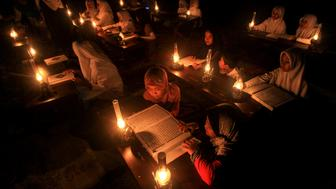 """Students read the Koran outdoors by oil lamp to celebrate """"Nuzul al-Koran"""" or """"The Revelation of the Koran"""", on the 17th day of the holy month of Ramadan that the first verse of the Koran was revealed to Prophet Muhammad, in Solo, Central Java, Indonesia June 21, 2016 in this photo taken by Antara Foto.  Antara Foto/Maulana Surya/ via REUTERSATTENTION EDITORS - THIS IMAGE HAS BEEN SUPPLIED BY A THIRD PARTY. IT IS DISTRIBUTED, EXACTLY AS RECEIVED BY REUTERS, AS A SERVICE TO CLIENTS. FOR EDITORIAL USE ONLY. NOT FOR SALE FOR MARKETING OR ADVERTISING CAMPAIGNS MANDATORY CREDIT. INDONESIA OUT. NO COMMERCIAL OR EDITORIAL SALES IN INDONESIA.     TPX IMAGES OF THE DAY"""