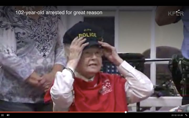 The do-gooder is seen trying on a St Louis Police Department hat after handing out handmade gifts to some of the senior center's guests.