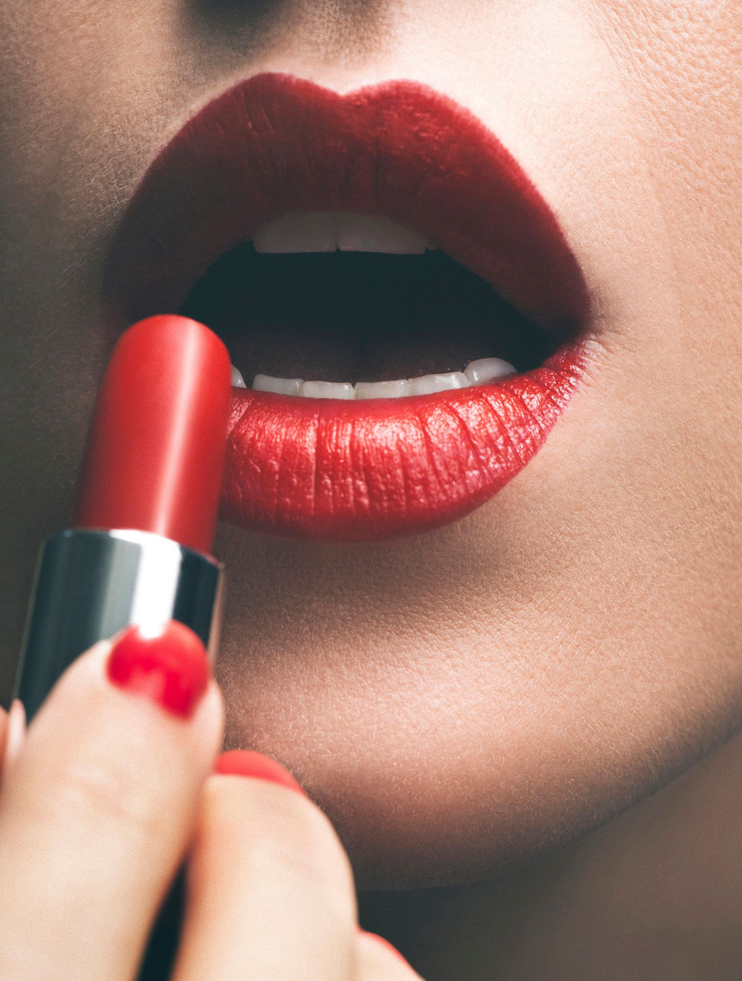 Close up of woman applying red lipstick