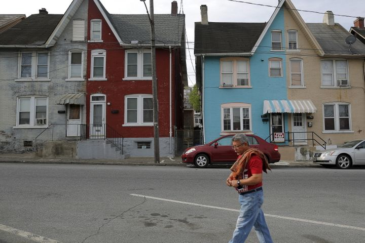 A man walks past multicolored homes that face the now-closed Bethlehem Steel mill in Bethlehem, Pennsylvania, on April 2