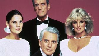 American actor Rock Hudson, center background, poses with fellow cast members John Forsythe, seated at center, Linda Evans, right, and Ali MacGraw, left, in Dynasty US TV series in 1985. (AP Photo)