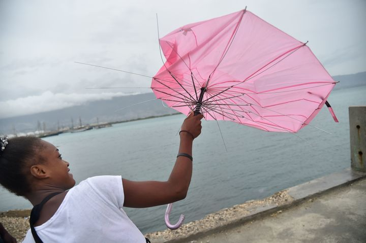 A girl tries to repair her umbrella that was broken by the wind in the commune of Cite Soleil in the Haitian capital of Port-