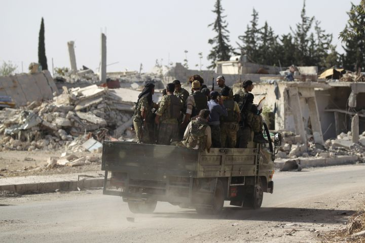 Rebel fighters drive past damaged buildings in al-Rai town, northern Aleppo countryside, Syria October 2, 2016.