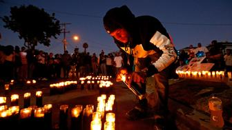 LOS ANGELES, CA - OCTOBER 2, 2016: Jeromy Jackson, lights candles for his best friend Carnell Snell Jr., 18, who was fatally shot by LAPD police Saturday after a vehicle pursuit, at at vigil in Los Angeles, Calif., on Oct. 2, 2016. The candles spell out Long Live C.J. (Photo by Gary Coronado / Los Angeles Times via Getty Images)