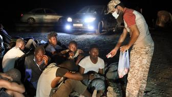 Migrants from African origin receive food at the port in the Libyan town of Garabulli, east of Tripoli, on October 3, 2016 after they were rescued by the Libyan coast guard police as their small boat capsized. Two children and nine women died on when a small boat carrying migrants to Italy capsized off the shore of Libya, a coastguard official said. The official, who asked not to be identified, told AFP the victims were among 160 people crammed aboard the boat that went down off Garabulli.    / AFP / MAHMUD TURKIA        (Photo credit should read MAHMUD TURKIA/AFP/Getty Images)