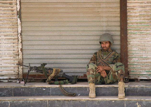 An Afghan National Army (ANA) soldier sits in front of a closed shop in the downtown of Kunduz city,...
