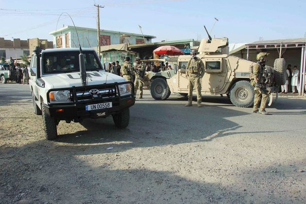 Afghan security forces keep watch in front of their armored vehicle in Kunduz city, Afghanistan on October...
