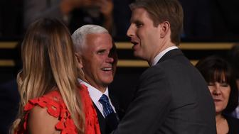 Republican Vice Presidential candidate, Indiana Governor Mike Pence (C) is greeted by Eric Trump (R), son of Republican presidential candidate Donald Trump, on the floor of the Republican National Convention on July 19, 2016 at Quicken Loans Arena in Cleveland, Ohio. The Republican Party formally nominated Donald Trump for president of the United States, capping a roller-coaster campaign that saw the billionaire tycoon defeat 16 White House rivals. / AFP / Timothy A. CLARY        (Photo credit should read TIMOTHY A. CLARY/AFP/Getty Images)