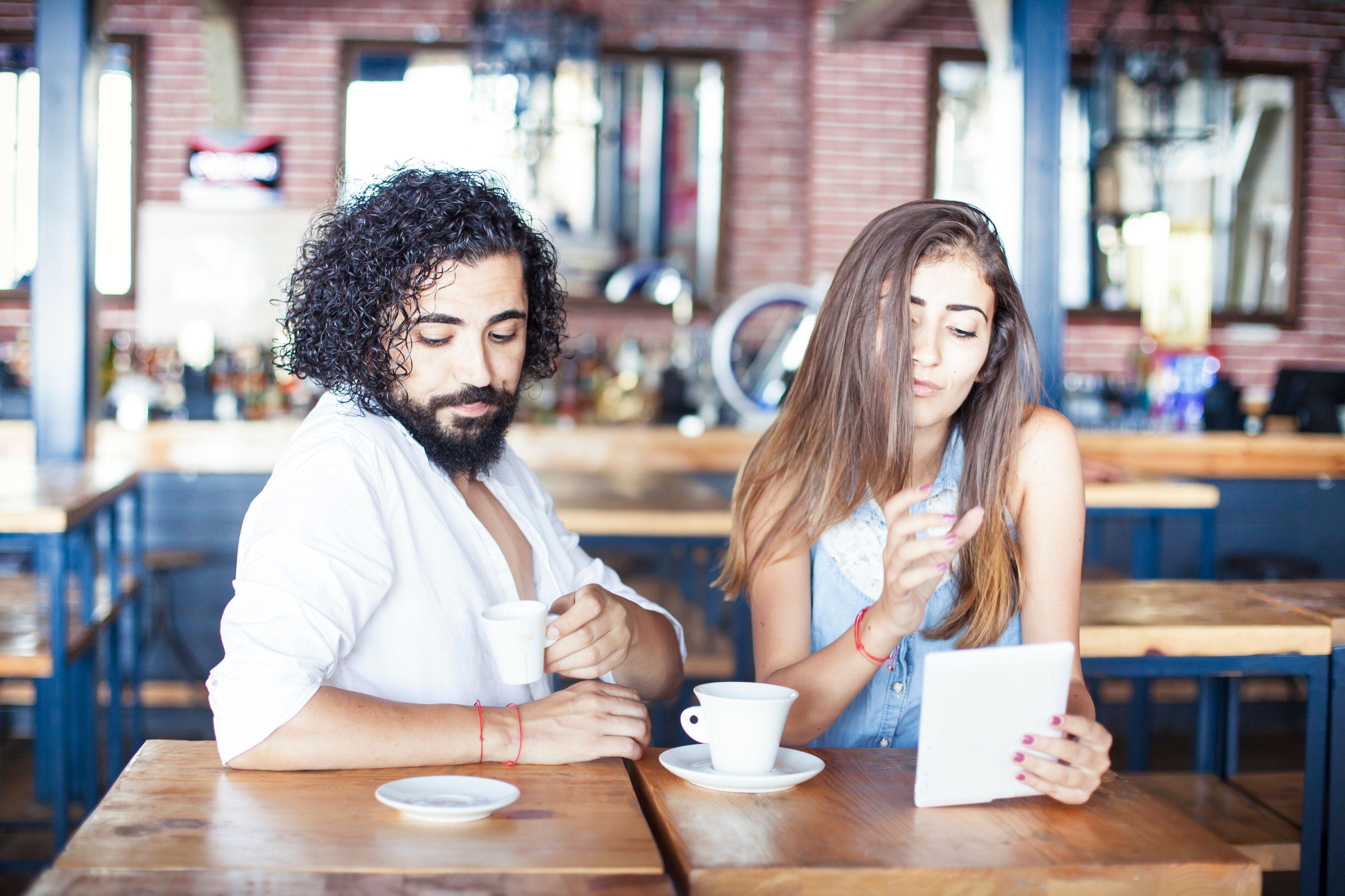 Young couple in a cafe. People in the image are  worn with casual clothes. woman  is holding tablet pc