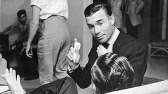 Dominican diplomat and socialite Porfirio Rubirosa (1909 - 1965) gestures with one hand and adjusts his tie with the other while he speaks to an unidentifed man, 1950s. (Photo by Hulton Archive/Getty Images)