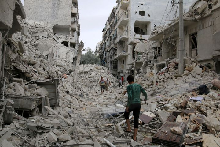 People walk through rubble caused by airstrikes in Aleppo's rebel-held Tariq al-Bab neighborhood on Sept.