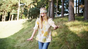 Blindfolded woman walking by woods