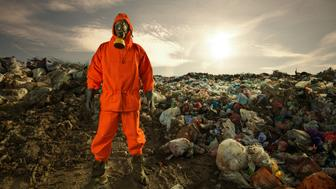 Environmental engineer standing on the landfill in front of the municipal waste.