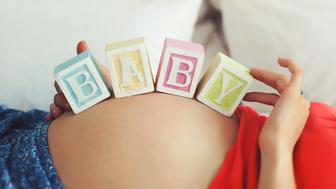 Pregnant Caucasian woman balancing with hands wooden toy blocks with letters baby on her baby bump in bed.