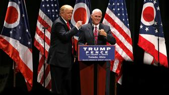 Republican presidential nominee Donald Trump brings vice presidential nominee Mike Pence onstage as he rallies with supporters in Toledo, Ohio, U.S., September 21, 2016. REUTERS/Jonathan Ernst