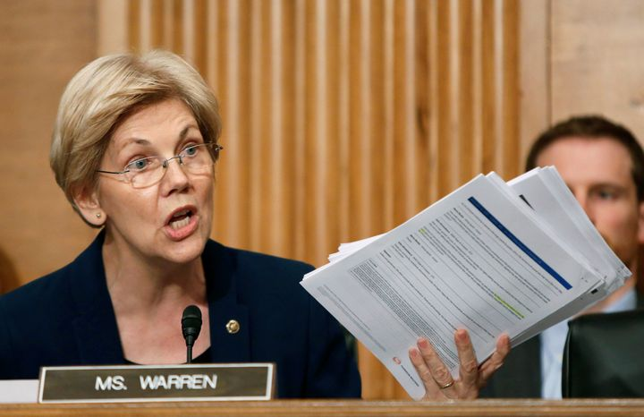 U.S. Senator Elizabeth Warren (D-MA) shows company documents to Wells Fargo CEO John Stumpf during his testimony before a Sen