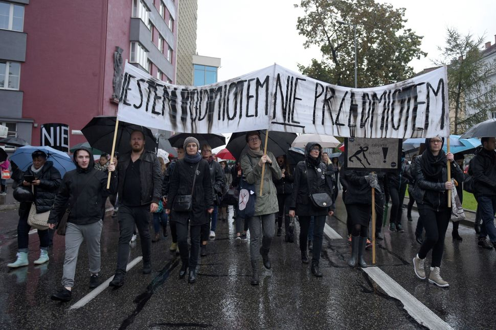 """Polish men and womenmarch through the streets of Krakow with a banner that says """"I'm a subject, not an object."""""""