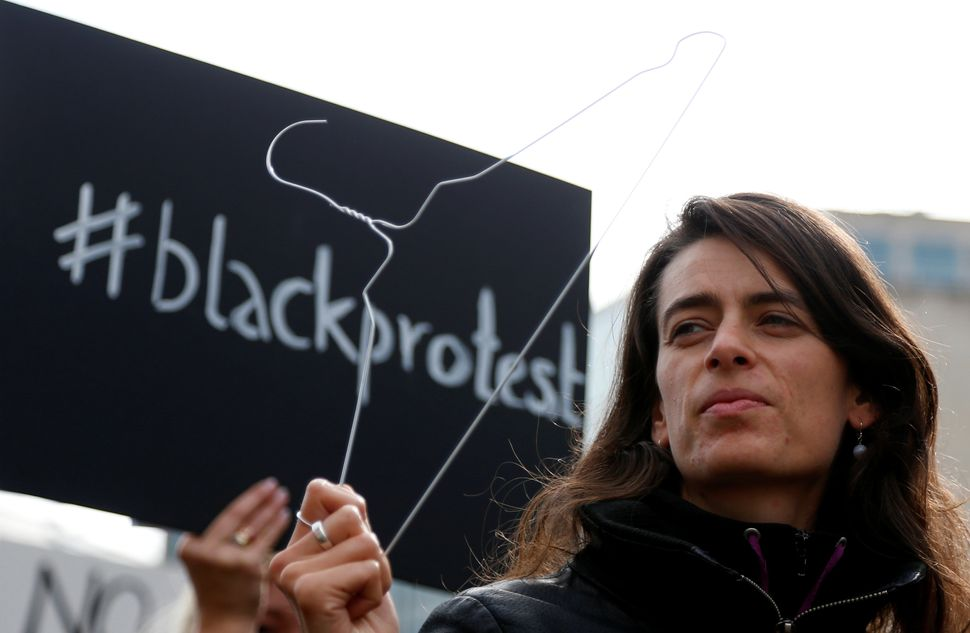 A woman protests with a clothes hanger in Brussels, the capital of the European Union.