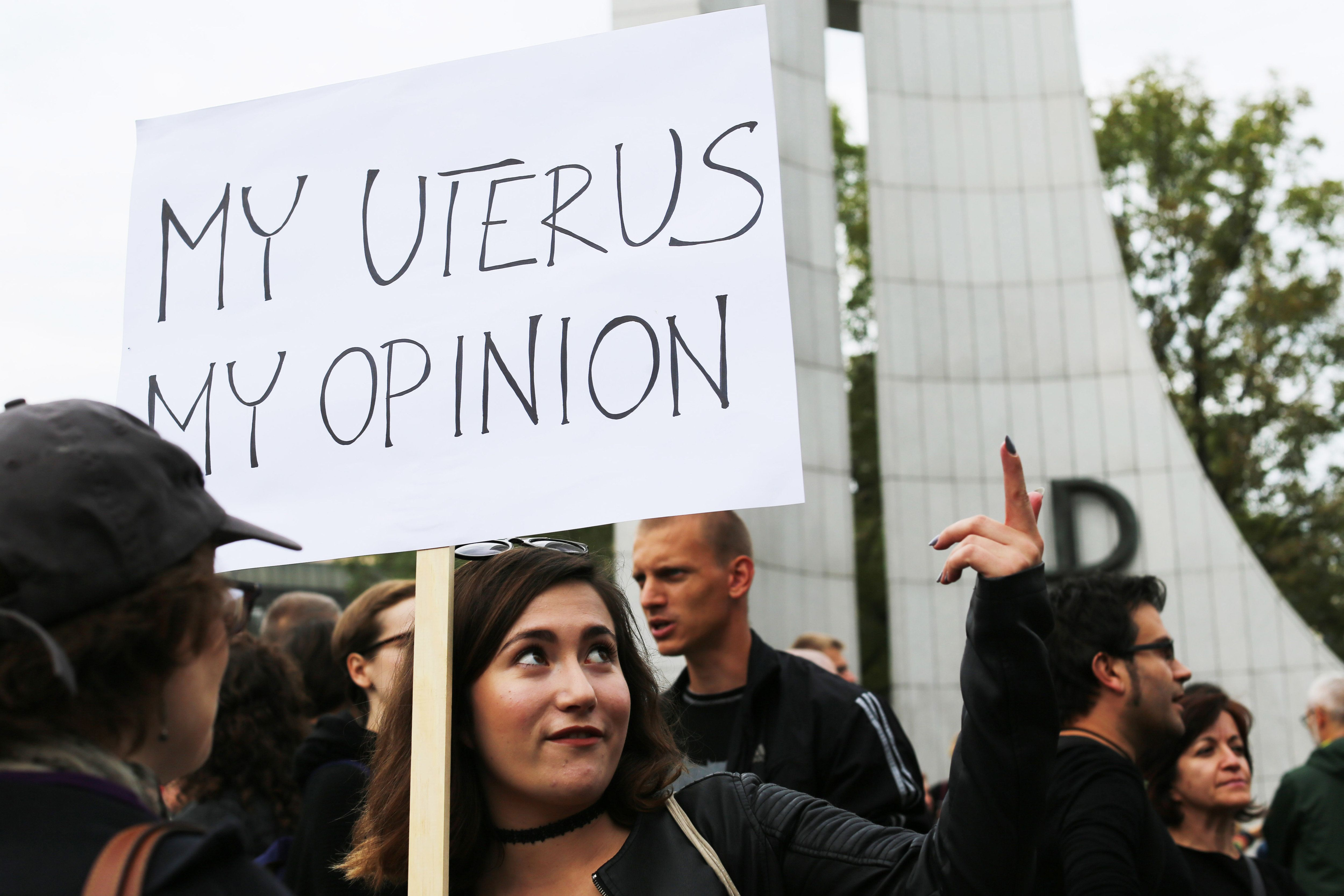 WARSAW, POLAND - 2016/10/01: A woman holds up a sign  reads, 'My uterus, My Opinions'  during a protest in front of the Polish parliament against a legislative project that will effectively outlaw all abortions under every circumstance, including rape and incest. The proposed project also seeks jail time for women who abort. Protesters united under the slogan 'No More Jokes! My body, my decision' voicing anger that  this project was approved by the right-wing majority in Poland's parliament and will be further debated on. Meanwhile another project, backed by pro-choice politicians and groups, was rejected by the parliament in the first reading. (Photo by Anna Ferensowicz/Pacific Press/LightRocket via Getty Images)