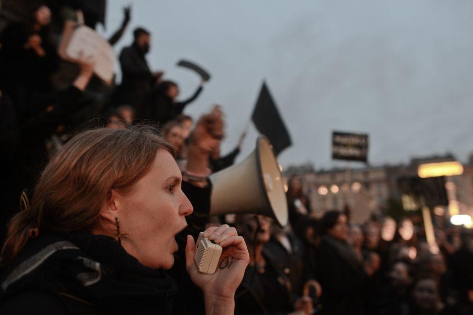Men and women chanting in Krakow's main square.