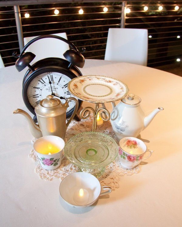 """Alice in Wonderland"" table with teacups and a clock."