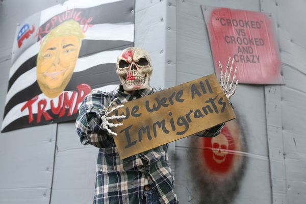 "One of the skeletons holds a sign saying, ""We were all immigrants."""