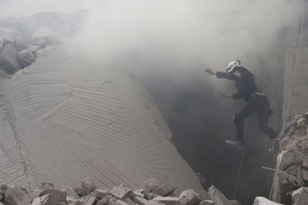 A civil defense member carries out a search and rescue operation over the wreckage of collapsed buildings...
