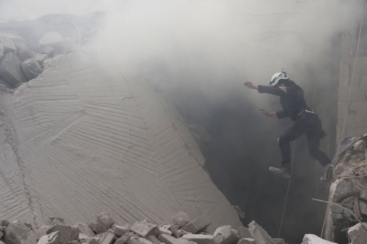 A civil defense member carries out a search and rescue operation over the wreckage of collapsed buildings in Aleppo.