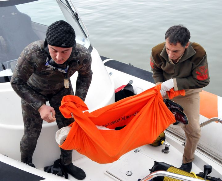 Turkish Coast Guard members carry the body of a refugee after a boat, which was carrying refugees, sank in the Aegean Sea on
