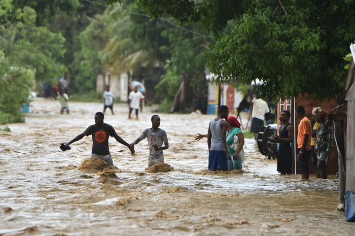 People try to cross the overflowing La Rouyonne river in the commune of Leogane, south of Port-au-Prince, Haiti, on Oct.