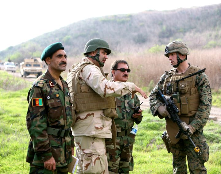 Afghan national army officers discuss lessons learned alongside Marines and Navy personnel while participating in combat scen