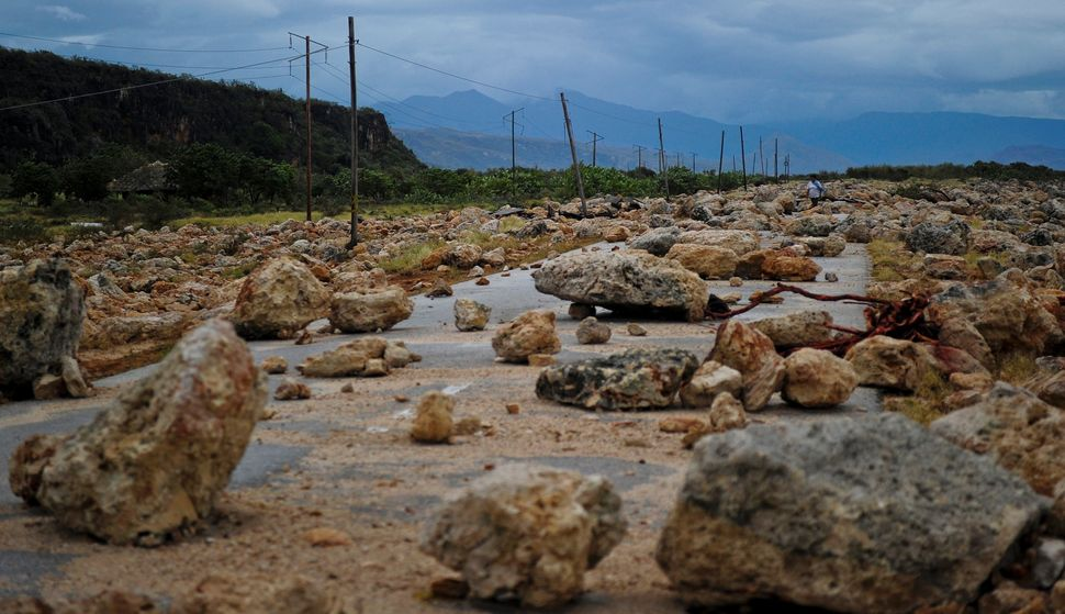 A road between Guantanamo and Baracoa in Cuba is left covered in rocks and rubble Wednesday after Hurricane Matthew pass