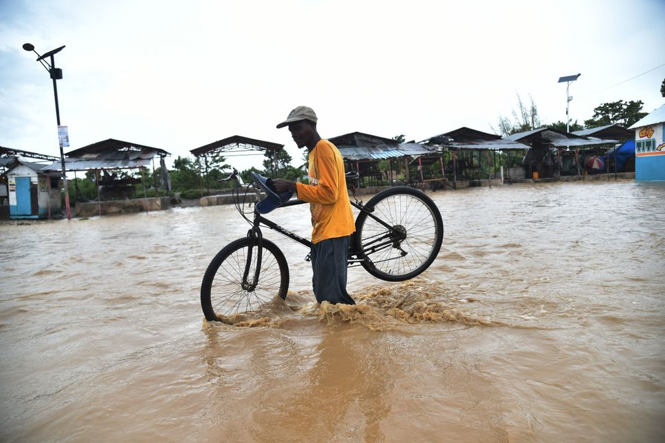 A man tries to cross the overflowing Rouyonne River inPort-au-Prince on Wednesday.