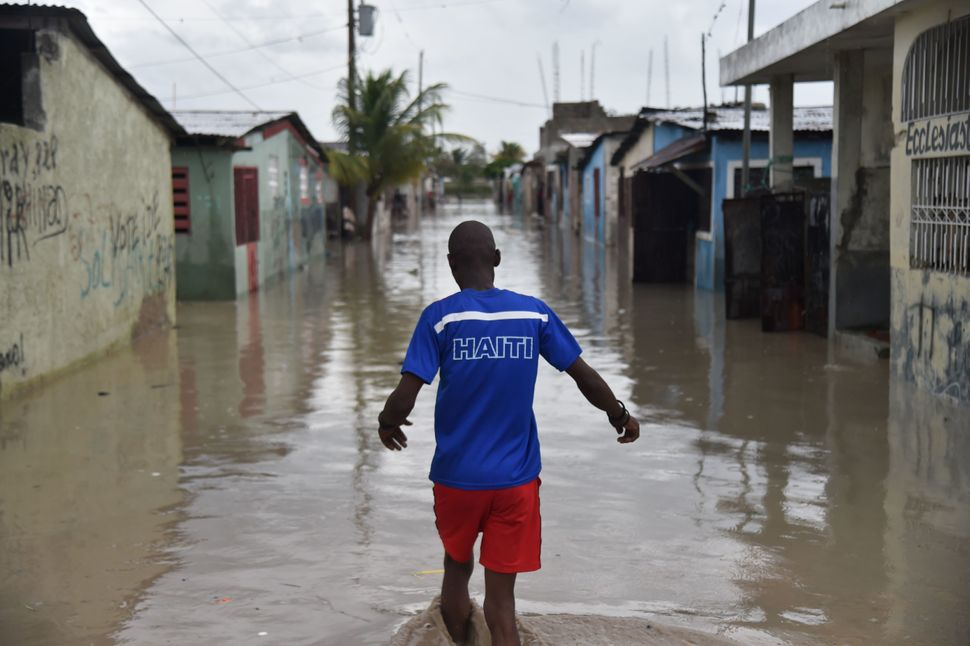 A man walks down the flooded street of aPort-au-Prince commune on Tuesday.