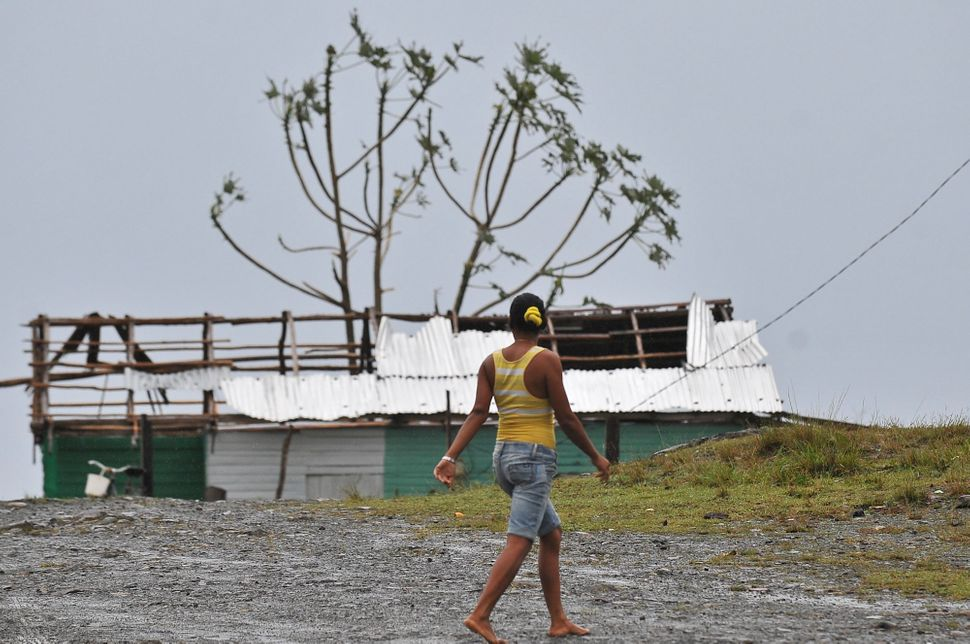 A woman walks past damaged housing in the Carbonera community of Guantanamo, Cuba, on Wednesday.