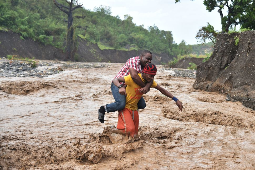 A man is carried across the La Digue river in Petit Goave, Haiti, on Wednesday.