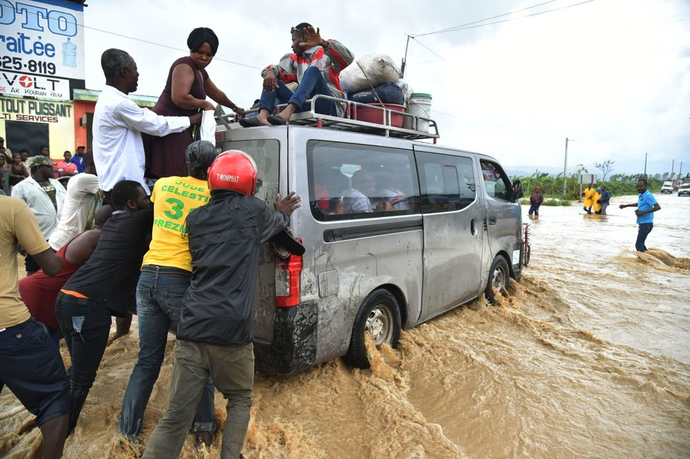 People try to cross the overflowing La Rouyonne river south of Port-au-Prince on Wednesday.