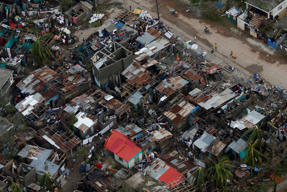 People walk down the street next to destroyed houses in Jeremie, Haiti, on Wednesday.