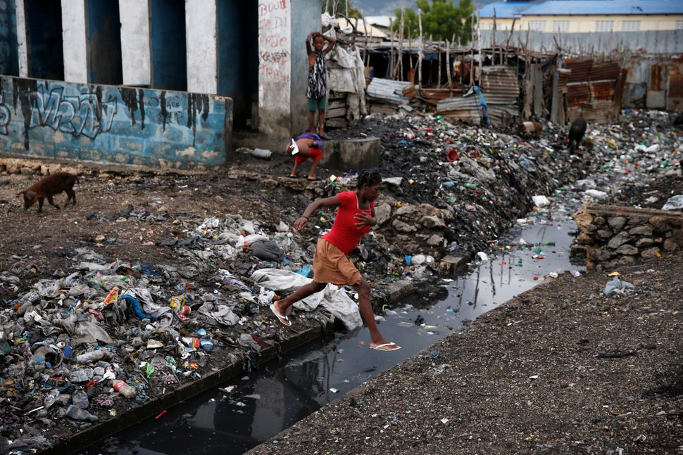 A woman crosses over a water canal in Port-au-Prince, Haiti, on Wednesday.