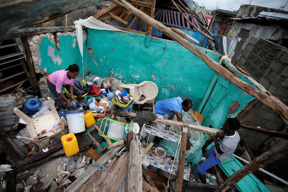 People clear a house destroyed by Hurricane Matthew in Les Cayes, Haiti, on Wednesday.