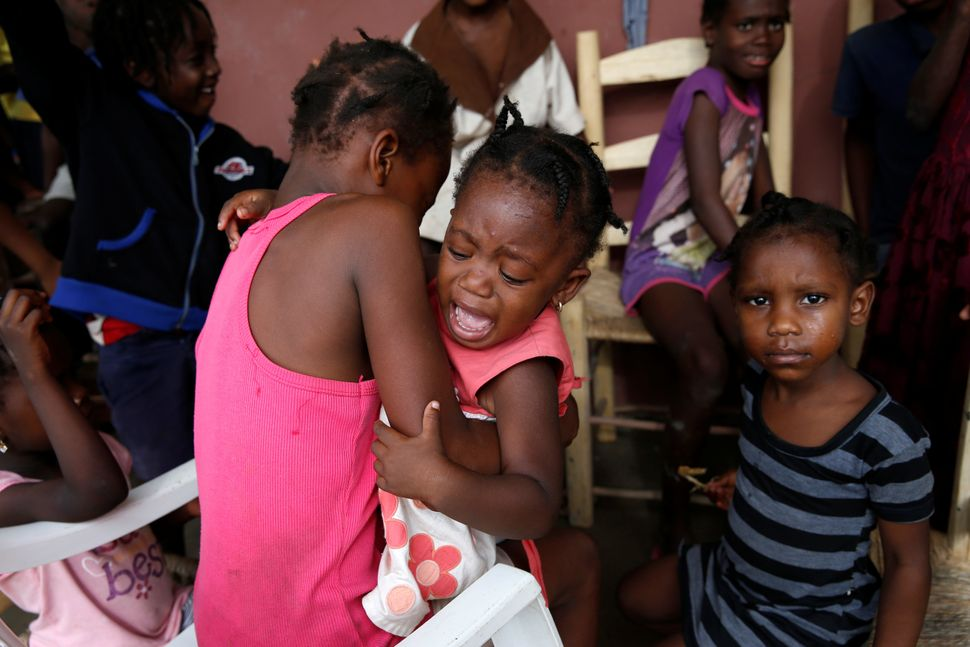 A girl cries, surrounded by relatives, at a partially destroyed school on Wednesday after the hurricane passed Jeremie,