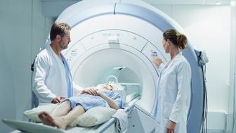 Male and female doctors preparing patient for MRI scan in hospital