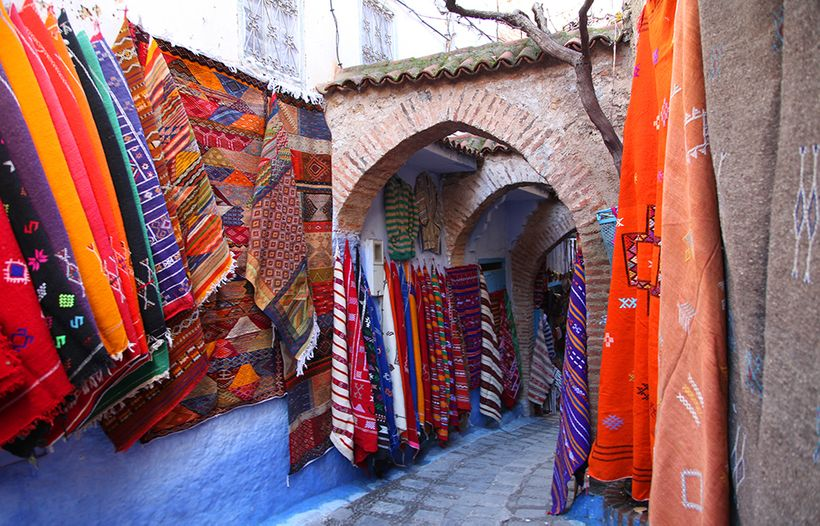 Colourful wool woven fabrics line the streets of Chefchaouen, Morocco