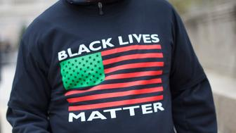 BALTIMORE, MD - APRIL 25:  Monte Jackson drinks an energy drink with a newly purchased t-shirt stating 'Black Lives Matter' outside City Hall before a protest in honor of Freddie Gray April 25, 2015 in Baltimore, Maryland. Gray, 25, was arrested for possessing a switch blade knife April 12 outside the Gilmor Homes housing project on Baltimore's west side. According to his attorney, Gray died a week later in the hospital from a severe spinal cord injury he received while in police custody. (Photo by Mark Makela/Getty Images)