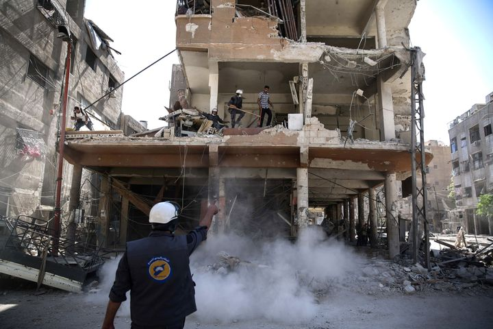 The White Helmets work around destroyed buildings following reported airstrikes on the rebel-held town of Douma, on the easte
