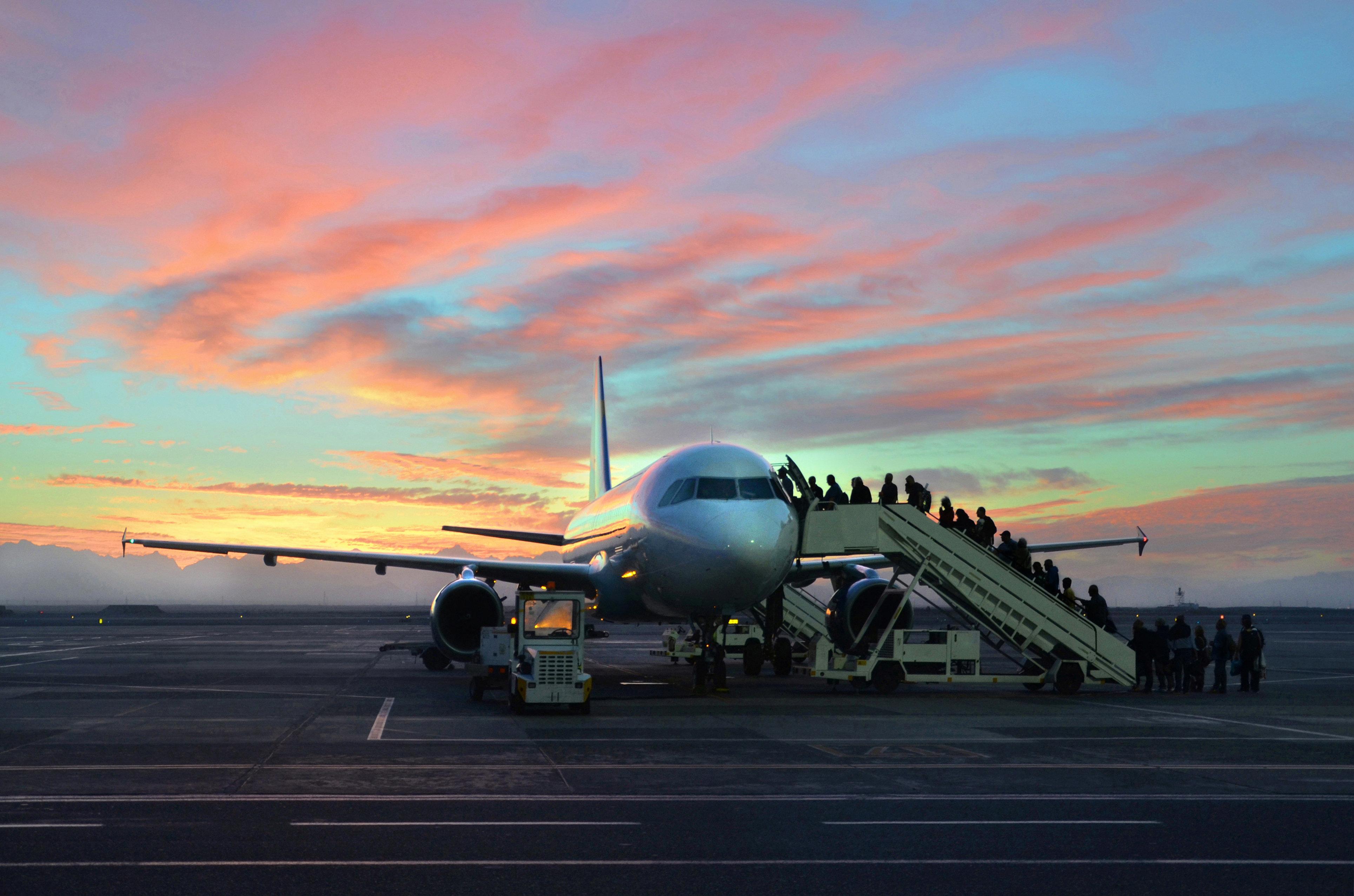 Passengers boarding a plane at sunset