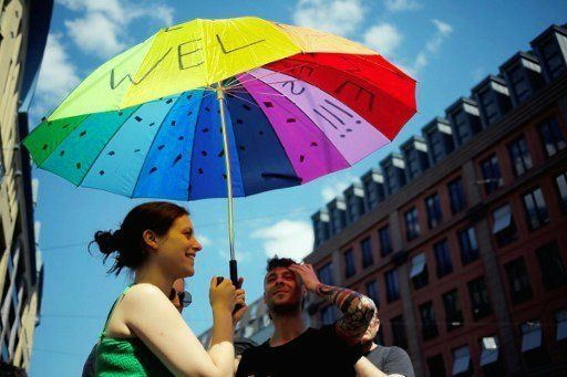 """Protesters hold an umbrella with """"Refugees Welcome"""" written on it in Berlin on May 7, 2016."""