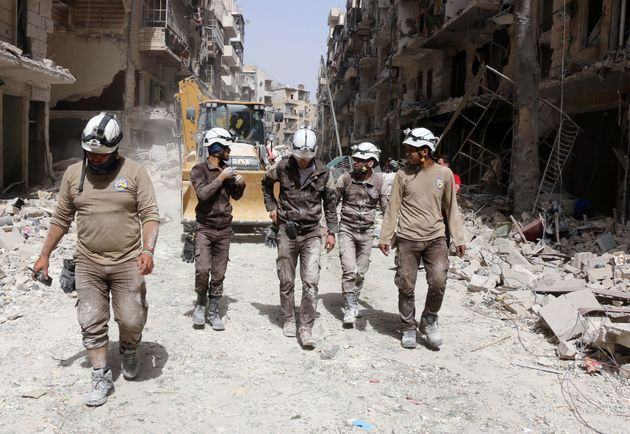 Members of the White Helmets walk amid the debris following a reported airstrike by Syrian government...